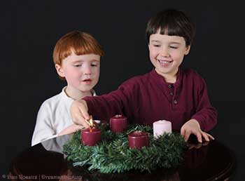 Two boys lighting the first purple candle on an advent wreath